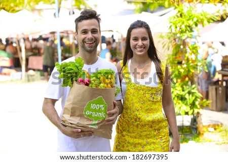 Happy couple  shopping at a open street market, carrying a shopping paper bag with a 100% organic certified label full of fruit and vegetables. - stock photo