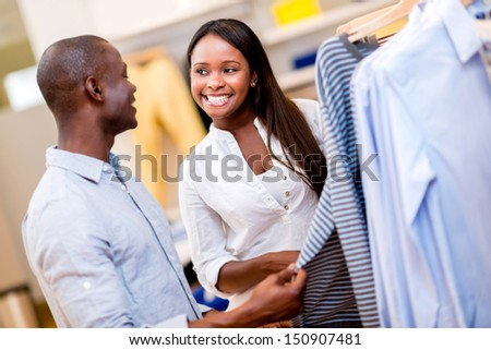 Happy couple shopping clothes at a retail store  - stock photo