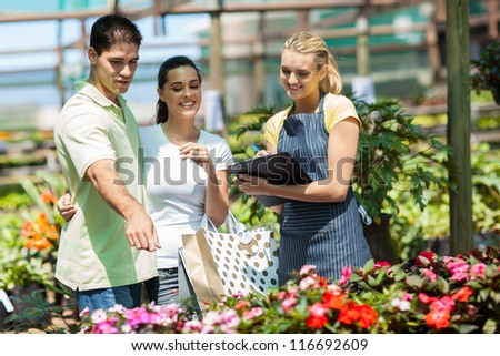 happy couple shopping for plants in greenhouse - stock photo