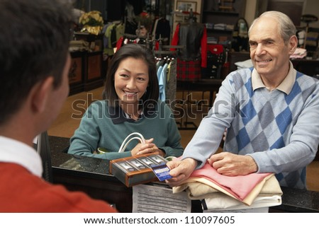 Happy couple shopping in store with credit card - stock photo