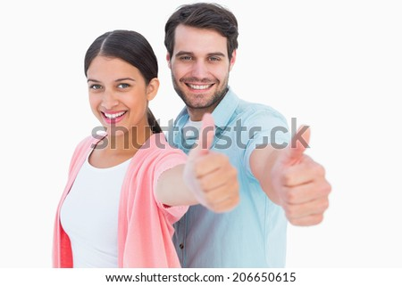 Happy couple showing thumbs up on white background - stock photo