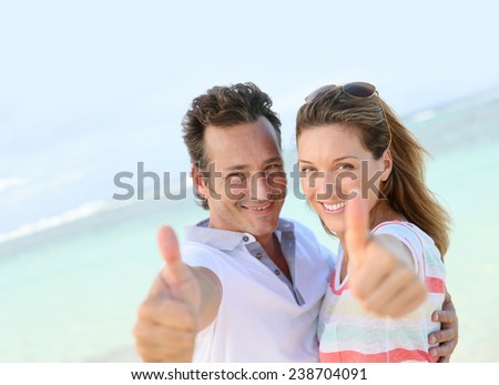 Happy couple showing thumbs up to camera - stock photo
