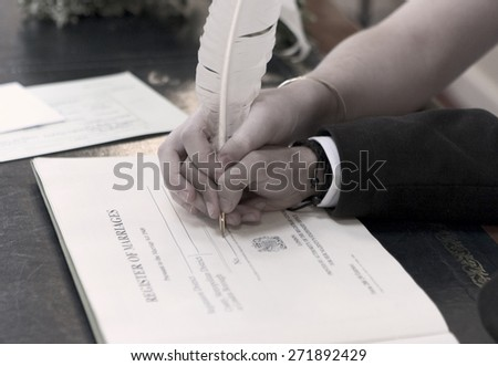 happy couple sign the register of marriages