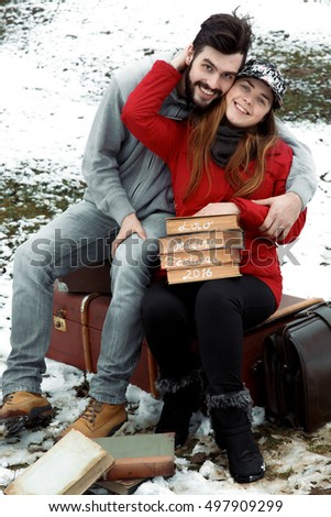 Happy couple sits on old suitcases in winter garden