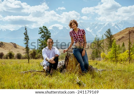Happy couple sits on the stump on background of mountains