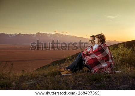 Happy couple sits on the top of the hill and hugging on background of mountains with glaciers  - stock photo
