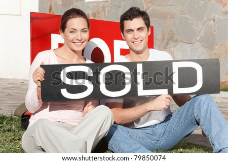 Happy couple sitting against their new house with sold sign - stock photo