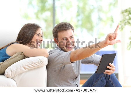Happy couple sitting and planning new decoration with a tablet on line at home with a window in the background - stock photo