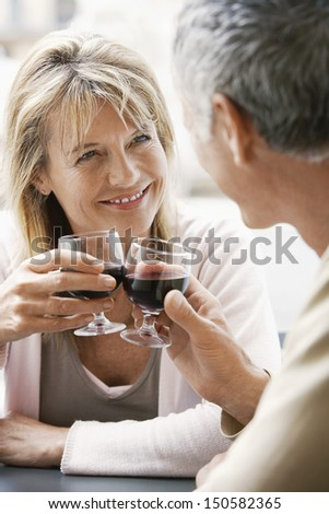 Happy couple sitting at outdoor cafe toasting wine glasses in Rome - stock photo