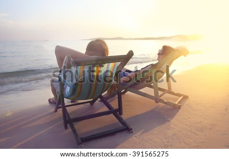 Happy couple sitting at sun chairs on the beach of Koh Samet at sunset, Thailand