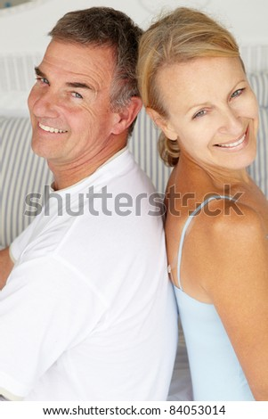Happy couple sitting back to back on bed - stock photo