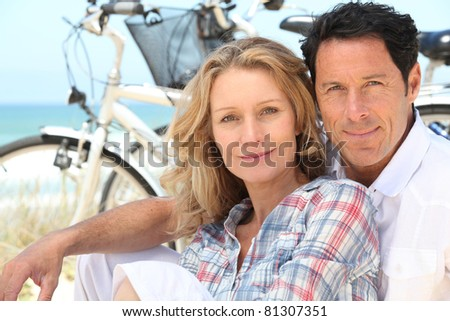 Happy couple sitting by the beach with their bikes - stock photo