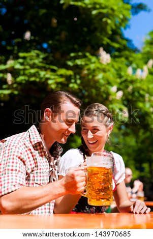 Happy Couple sitting in Beer garden and enjoy the beer and the sun - stock photo