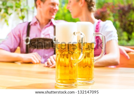 Happy Couple sitting in Beer garden in summer and enjoying a glass of beer and the sun, in the voreground standing two glasses - stock photo