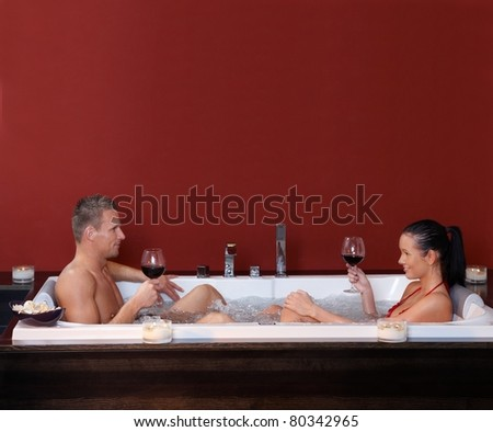 Happy couple sitting in jacuzzi together, drinking red wine, smiling.? - stock photo