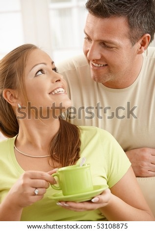 Happy couple sitting in living room, woman holding tea cup with two hands looking up at man smiling.