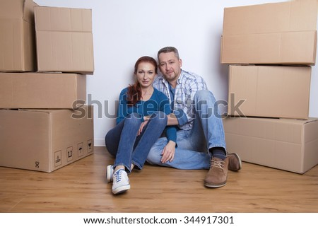 happy couple sitting in their new home with cardboard boxes - stock photo