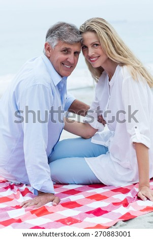 Happy couple sitting on a blanket and smiling at camera at the beach - stock photo