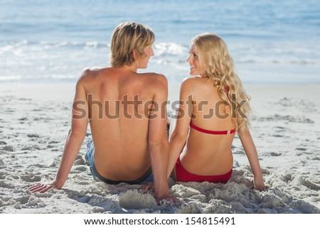 Happy couple sitting on beach and looking at each other