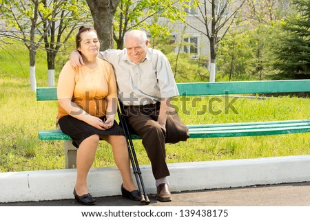 Happy couple sitting on bench and talking in the park - stock photo