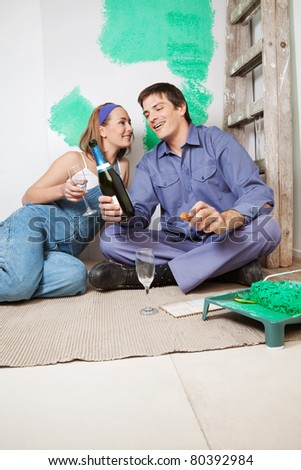 Happy couple sitting on floor and having champagne