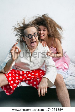 Happy couple sitting on the bed - stock photo