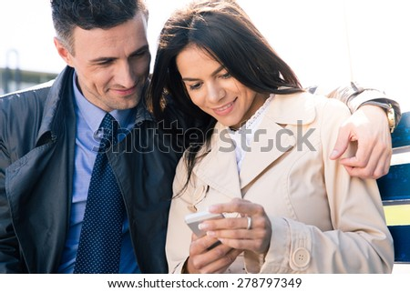 Happy couple sitting on the bench and using smartphone outdoors - stock photo