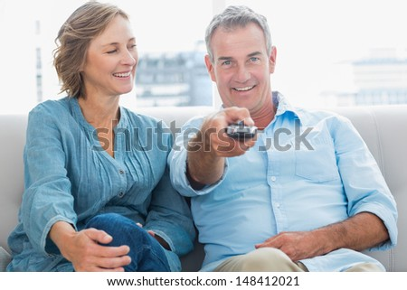 Happy couple sitting on the couch watching tv at home in the living room - stock photo