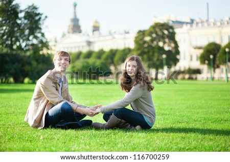 Happy couple sitting on the grass together - stock photo