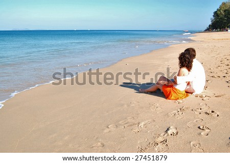 Happy couple sitting on the tropical beach