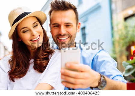 Happy couple sitting outdoors in cafe, looking at the phone - stock photo