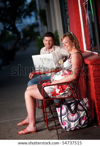 Happy couple sitting outside a cafe with laptop computer - stock photo
