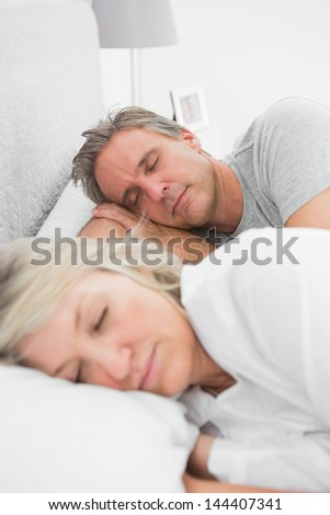 Happy couple sleeping peacefully at home in bed