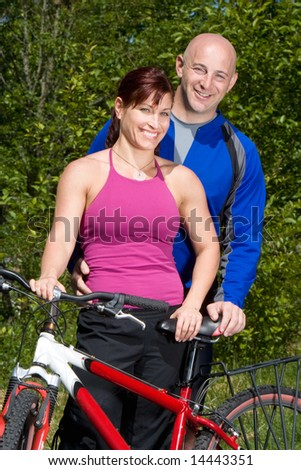 Happy couple smile while posing next to a mountain bike. Vertically framed photograph. - stock photo
