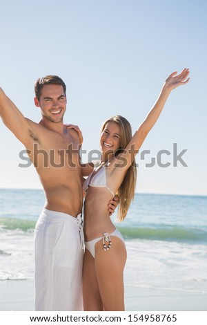 Happy couple smiling and waving at camera on the beach - stock photo