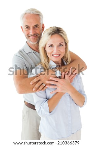 Happy couple smiling at camera and embracing on white background - stock photo