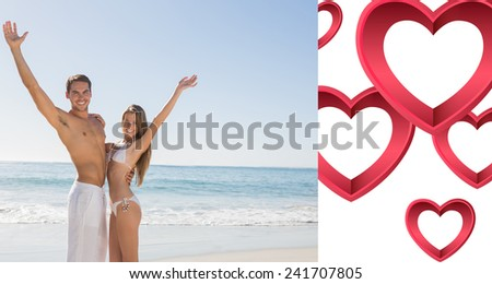 Happy couple smiling at camera and waving against pink hearts - stock photo