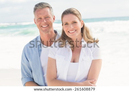 Happy couple smiling at camera at the beach