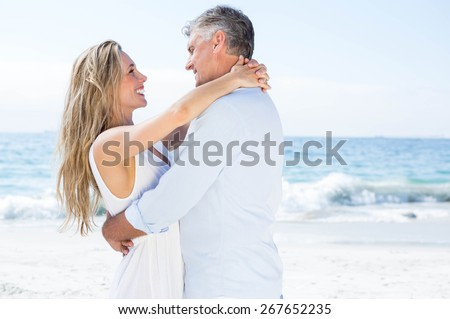 Happy couple smiling at each other by the sea at the beach - stock photo