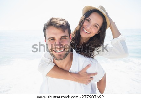 happy couple smiling at the beach - stock photo