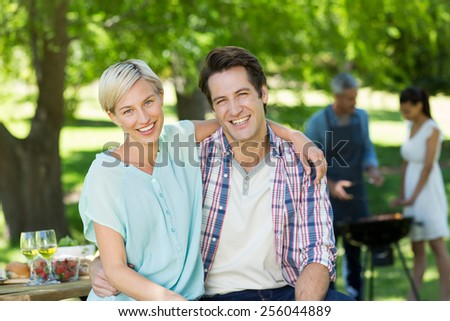 Happy couple smiling at the camera on a sunny day - stock photo
