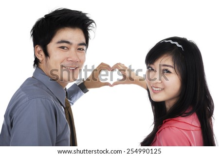 Happy couple smiling at the camera while showing heart shape with their hands, isolated on white - stock photo