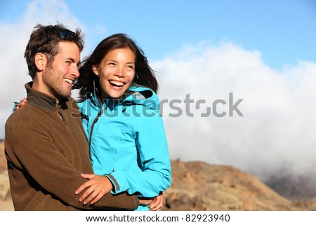 Happy couple smiling outdoors on hiking trip. Young mixed asian caucasian couple enjoying nature. - stock photo