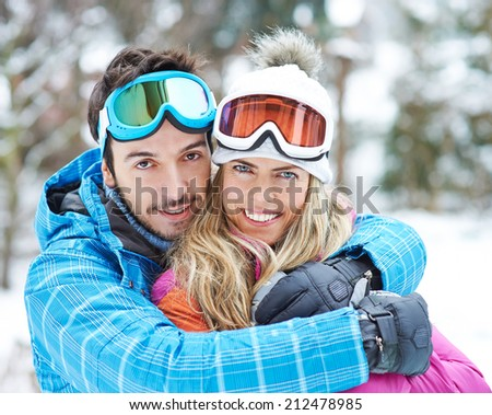 Happy couple smiling together on a ski trip in their winter holiday - stock photo