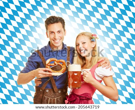 Happy couple smiling with beer at Oktoberfest in Bavaria - stock photo