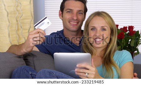 Happy couple smilng with credit card and tablet - stock photo