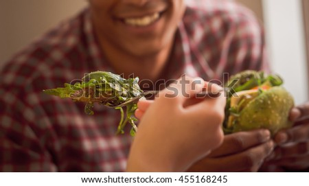 Happy couple spending free time in vegan restaurant or cafe. Closeup picture of lady feeding her boy-friend with vegan salad.