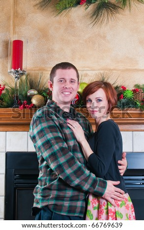 Happy couple spending time together in front of the fireplace at Christmas. - stock photo