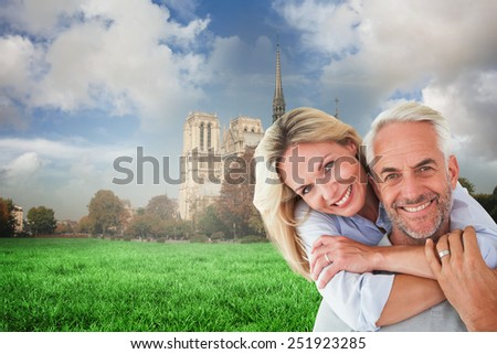 Happy couple standing and hugging against notre dame cathedral - stock photo