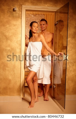 Happy couple standing at sauna door on healthy wellness program.? - stock photo